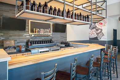 Pie Five's new prototype includes a bar, which serves local craft beer. Taps connect to kegs in a walk-in cooler behind the bar's back wall.