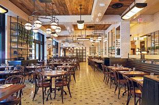 Front-of-the-house staff at The Smith, an American brasserie in Washington, D.C., access POS machines and supplies at stations designed as a feature in the main dining room. Photo by Clarence Butts