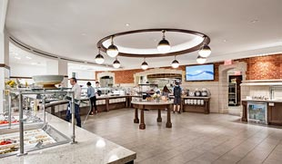 The center farm table and light fixtures around the circular cover ceiling at Pauli Murray College create a defining moment for circulation and provide a focal point. Photo by Peter Aaron/OTTO