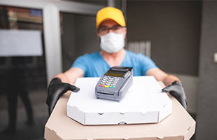 Pizza Deliverer with mask and credit card machine