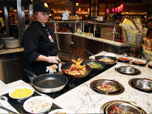 A staff member sautés vegetables and protein for fajitas at the Salad station.