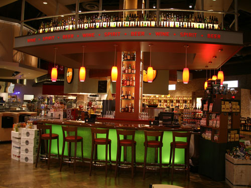 The Adult Beverage station displays bottles under bright lighting to attract customers. Counter seating is another attraction.