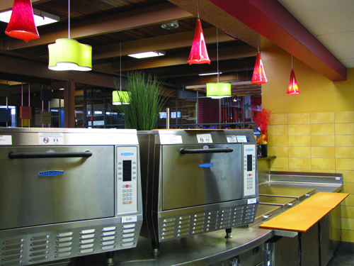 Two Rapid-cook ovens allow quick heating of subs and other items at RAMwich. To the right, staff make deli sandwiches on the cutting board.