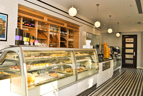 The retail bakery uses the same concrete floor tile, pendant lights and glazed subway tile as the main dining room. Custom-made display cabinets from Italy showcase the homemade pastries and ice cream. The custom-made maple wood shelving displays a variety of fresh baked breads and other merchandise.
