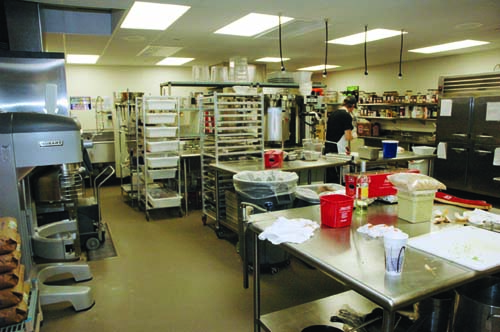 Shelving, worktables, refrigerators and a large mixer contribute to kitchen staff's efficiency as they prepare ingredients for the front-of-house stations.