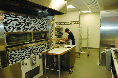 The back of the pizza station features a hearth oven and a surrounding tile wall.