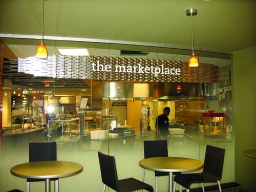 As customers approach The Marketplace, they can peer into the servery through floor-to-ceiling glass walls. The Marketplace signage is made of actual table knives that are adhered to brushed aluminum. The other stations' signage also incorporates repurposed materials: Stacks Deli, condiment bottles; Good to Go, plastic-coated paper carryout containers; Fizz and Sips, sipping straws; Hotspot, 12-inch skillets; Croutons, olive oil bottles with pour spouts; The Oven, small pizza peels; and Courtyard Grill, grill grates. Terrazzo flooring here is also used in the main street corridor connecting the building to the library, technology building and business school.