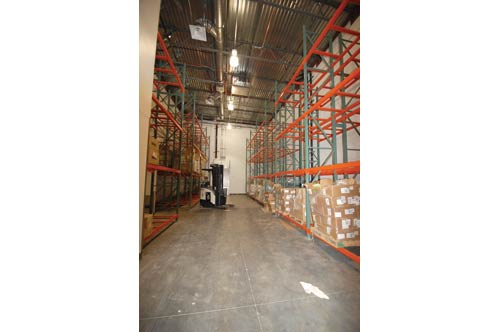 Bulk products are stored in a high-ceilinged room that occupies fewer square feet than a more horizontal space, reducing the cost of building materials.