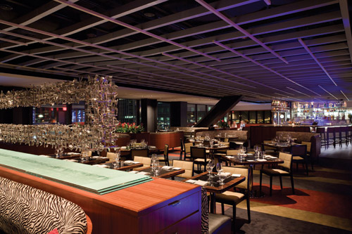 The restaurant after dark shows off the metal sculpture, art deco design and dramatic views. The architects designed the space to be asymmetrical. A metallic ceiling grill undulates across the bar, dining room and lounge, reinforcing the feeling of a limitless sky.
