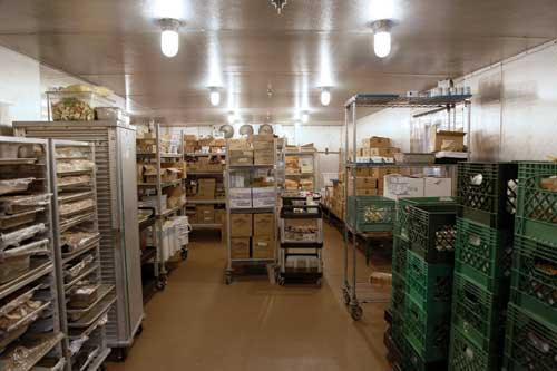 Durable shelving and containers hold food in the walk-in cooler until staff retrieve it for production.