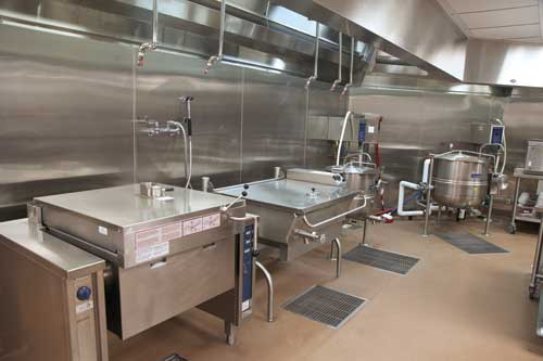 Back-of-house production equipment includes a pressure cooker, a tilting skillet and trunnion kettles. The hose on the stainless steel wall behind the equipment connects to a faucet device that automatically measures water for the cooking vessels.
