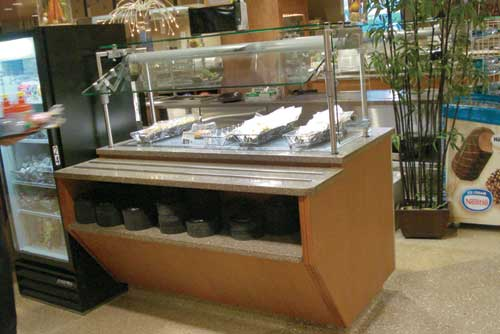 In the servery next to the cashier station, metal baskets display packaged house-made cookies next to the condiment refrigerator.