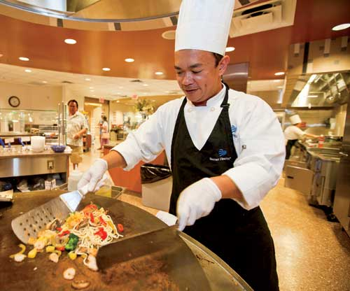 Delgado cooks customers' ingredient selections on the Mongolian grill.