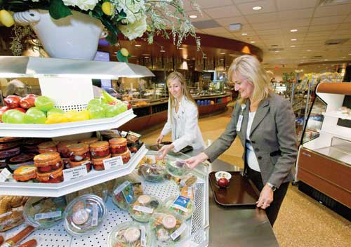 Clinical manager Carol Daniels and clinical dietitian Dominica Dieffenbach select salads, fruit, cheese and other upscale packaged foods at a display tower. Spelman and the designers used AJ's, a local upscale market, as a model for retail merchandising.