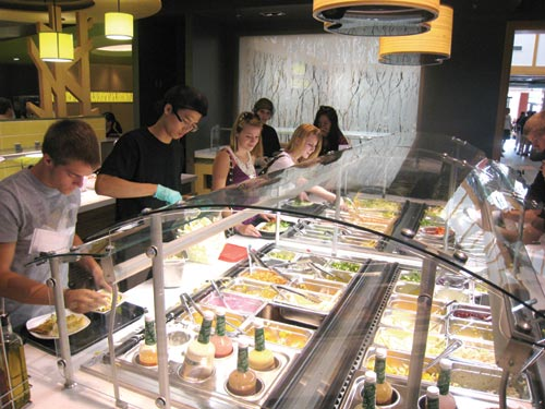 Customers select salad ingredients at both sides of the salad station.