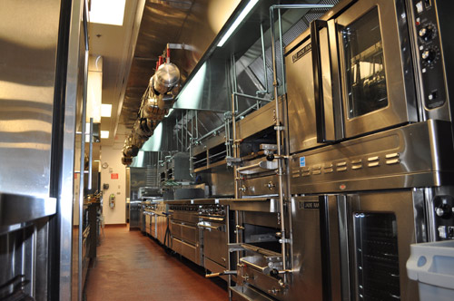 The cookline includes a double-deck convection oven, a double-deck infrared broiler, sauté range, flattop, fryers, two French-top ranges and a conveyor oven. Refrigerated drawers sit beneath the flattop and French-top ranges, and convection ovens sit beneath the sauté range. Cheese melters are above. The chef's counter is at the left with two refrigerated rails, a hot bain marie, one of three check printers, and lighting on the top and lower shelving so no shadows are cast on the food and the space is visible for thorough cleaning.
