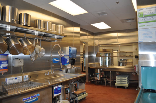 In the dishroom, pots and pans are soaked at the left and a low-water-usage dishwasher sits at the right. One waste collector is positioned at the left and another at the soiled-dish table in the center of the photo.