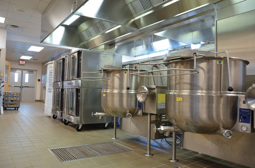 Staff use kettles and convection ovens for many of the menu items. The utility distribution system on the wall behind contributes to the kitchen's space- and energy-saving attributes and will give staff flexibility if they decide to change out equipment in the future.