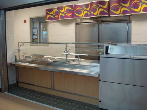 At the serving counter, menu items are kept at proper temperatures in steam wells and a frost top as students walk along and make selections.