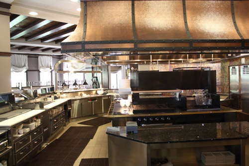 Inside deep blu, the hand-pounded copper hood provides exhaust control and a decorative element that ties in with an outside bar resembling a Spanish ship. The charcoal granite finish and brass trim, straps hanging from the hood and raised panel doors at the chef's table are also derived from Spanish décor.