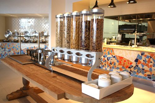 Also at Tesoro Cove, a wood table displays cereal dispensers. At left, induction coolers hold pans with bacon, sausage and other hot breakfast items. Every service counter is designed to look like a piece of furniture so it becomes part of the décor.