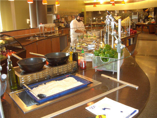 Chefs prepare customized salads at the farmer's market station using ingredients held in cold pans and prepared in induction cooktops.