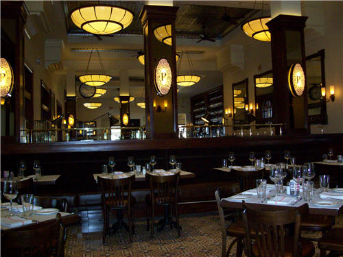 "The dark mahogany millwork and sconces with the ""P"" on the pillars are a recurring element throughout the restaurant's dining areas and bar. The antique clock, another traditional brasserie element, hangs at left. The bar stands at right."