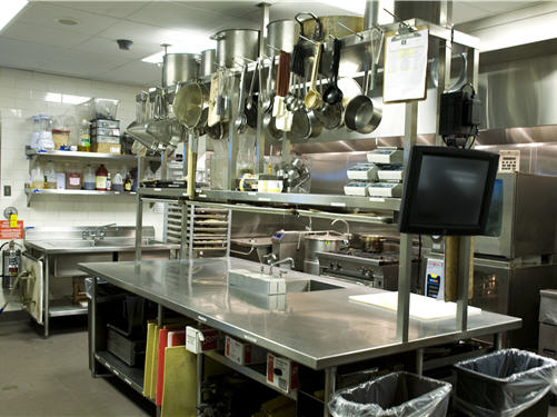 In the back-of-house kitchen, sinks are strategically placed with work tables so staff have access whenever needed. Utensils hang from above to conserve space.