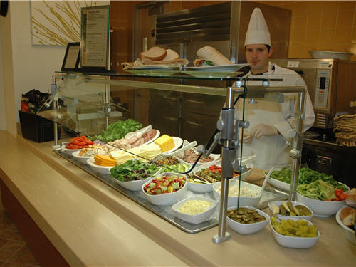 A chef presents deli fare over ice in a cold-serving unit. Sandwiches can be toasted in a panini oven at this station.