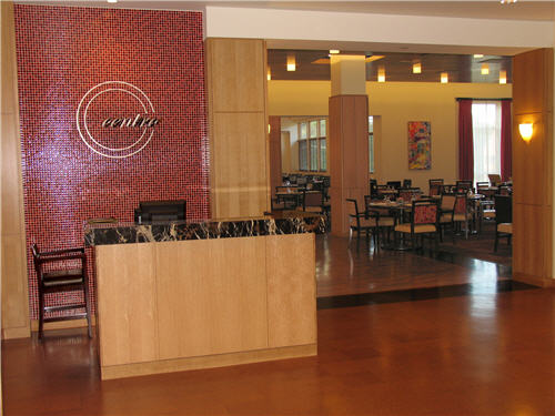 When guests approach Centro, a hostess   greets them. The display kitchen sits behind the Centro signage. Guests can   eat at the more informal dining area, shown here, or a formal dining   room.