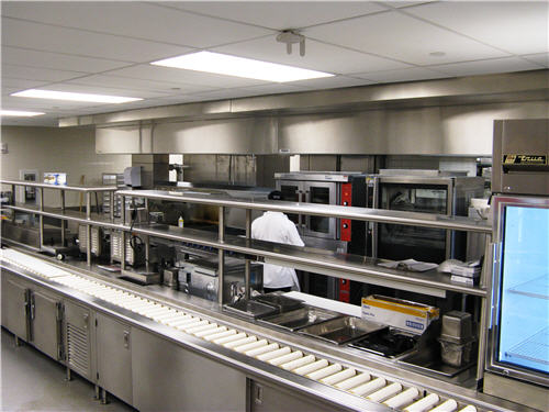 The room-service section of the kitchen includes a range, griddle, convection oven, rotisserie oven, fryer, three upright coolers and a tray-assembly line.
