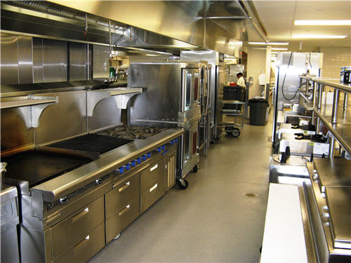 The hot line features a flat-top griddle, charbroiler, a range with oven beneath and combi-ovens.