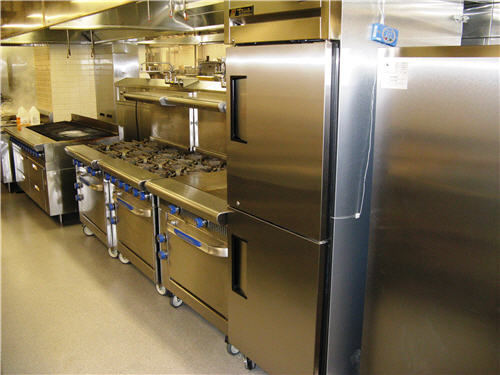 Reach-in refrigerators, a flat-top griddle, ranges, and charbroiler produce menu items for patient trays and cafeterias.