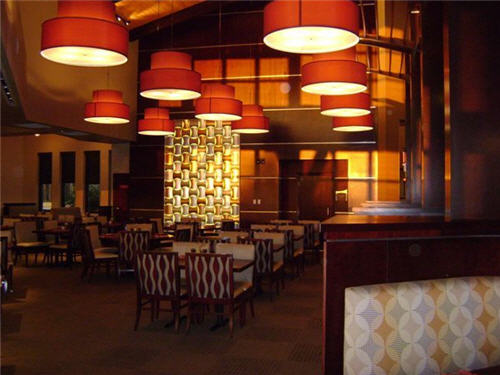 The restaurants main dining room contains wood, chrome and other textures and large fixtures with LED lighting that combine to add vibrancy to the space. The main dining room sits under the slanted roof.