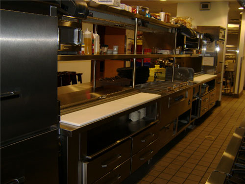 A warming drawer under the hot wells can serve as back-up for holding potatoes or other dishes. Another holding pan sits near the garde manger prep. Double shelving opens up storage space and creates good sight lines.