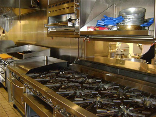 The pass window at right allows staff to pass menu items easily at the sauté station. Shelves hold sauté pans. The two six-burner ranges with a cheese melter above them? as well as a flat-top griddle, a char broiler and fryers constitute  the hot cook line.