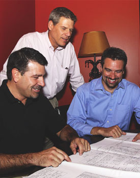 Cris Gross (right) looks over drawings with clients, Grand Traverse Pie Company Founder Mike Busely (left) and Co-owner Tim Rice (middle),